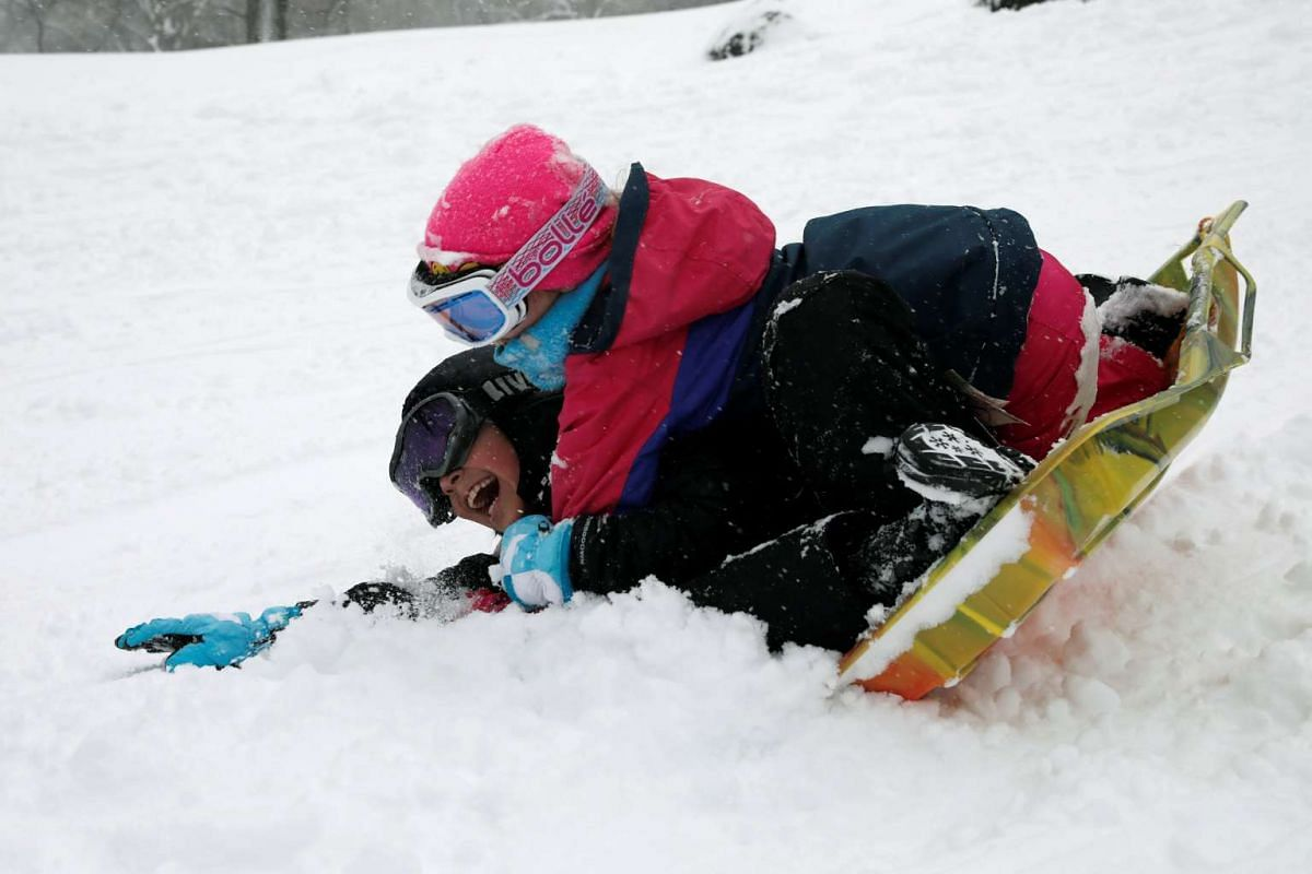 Two children riding a sled during a snow storm in Central Park on Manhattan's upper west side in New York City, US, on Feb 9, 2017.