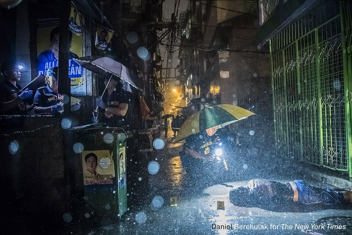 First Prize General News (Stories). Heavy rain pours as Scene of the Crime Operatives investigate inside an alley on Oct 11, 2016, where a victim, Romeo Joel Torres Fontanilla, 37, was killed by two unidentified gunmen riding motorcycles in the early