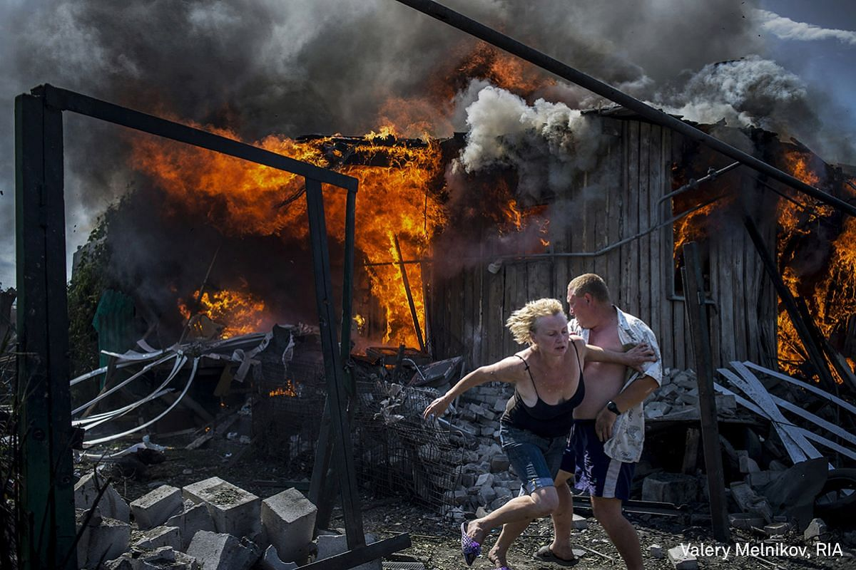 First Prize Long-Term Projects. Civilians escape from a fire at a house destroyed by the air attack in the Luhanskaya village.