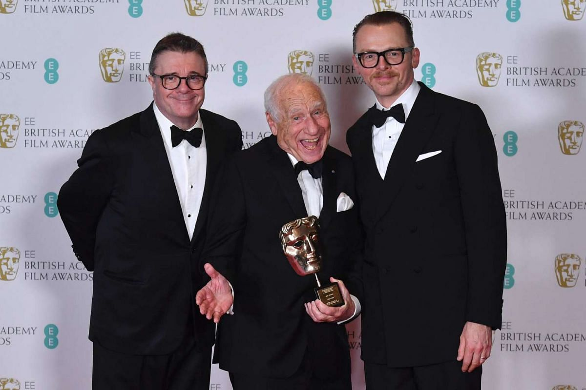 Actor and film-maker Mel Brooks (centre) poses with the Bafta Fellowship Award with presenters US actor Nathan Lane (left) and British actor Simon Pegg (right).
