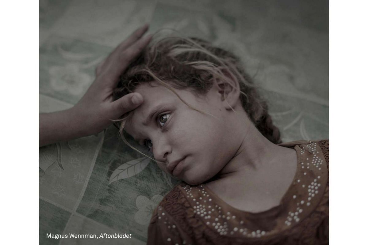 First Prize People (Singles) category. Maha, 5, lays on a dirty mattress as her mother strokes her hair in the overcrowded transit center in Debaga refugee camp after fleeing from the village Hawija outside Mosul, Iraq, seven days prior.