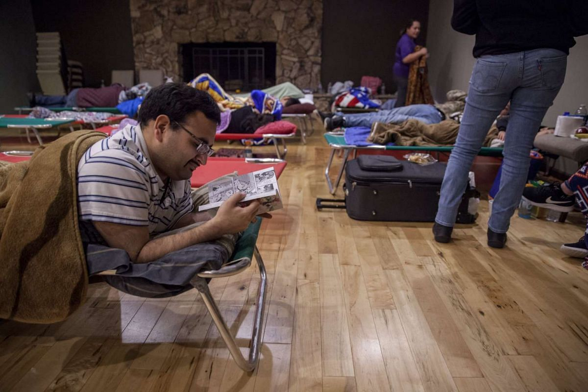 Evacuee Miguel Figueroa Jr. of Gridley, catches up on some reading at the  Neighborhood Church of Chico in Chico, California, on Feb 13, 2017.
