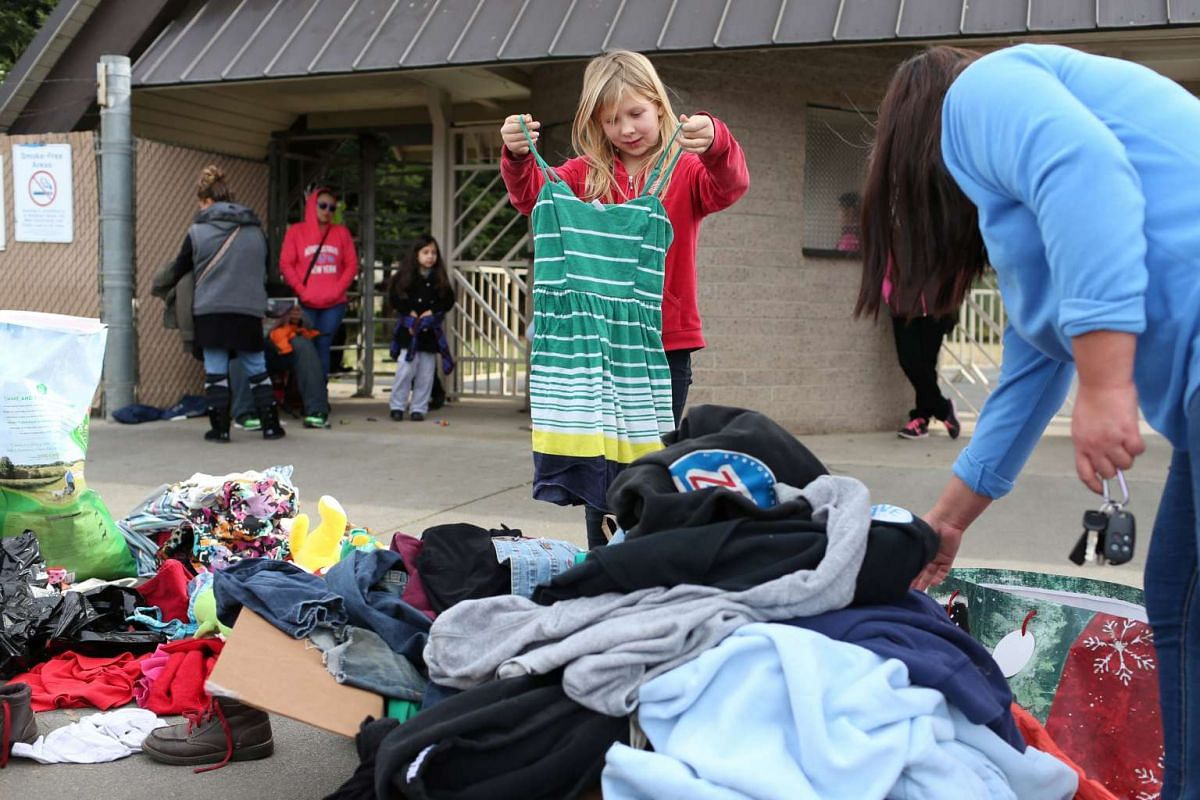 A girl sifting through donated clothing at a Red Cross relief center in Chico, California, on Feb 13, 2017.