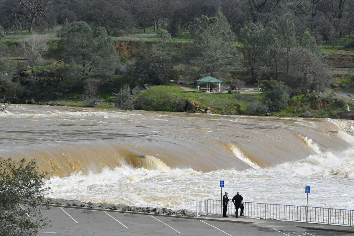 Police officers conferring as the Oroville Dam releases water down a spillway as an emergency measure , on Feb 13, 2017.