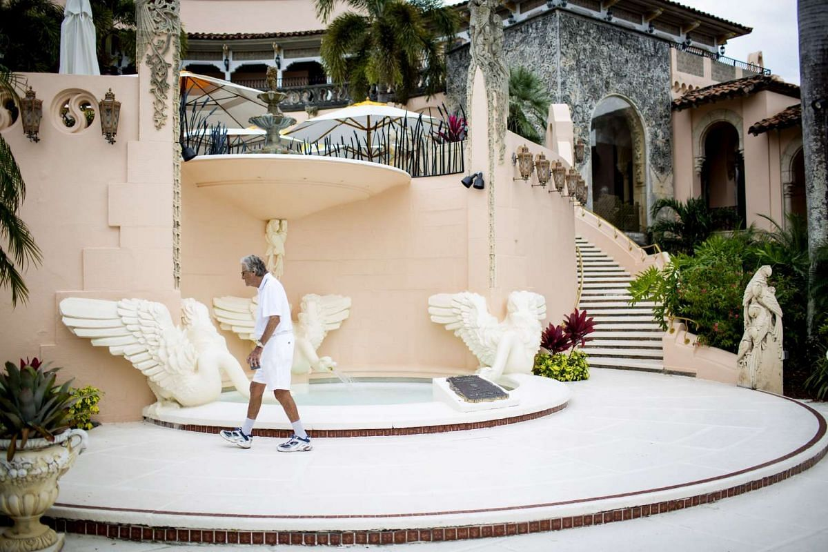 A man walking in front of a water feature at the Mar-a-Lago estate.