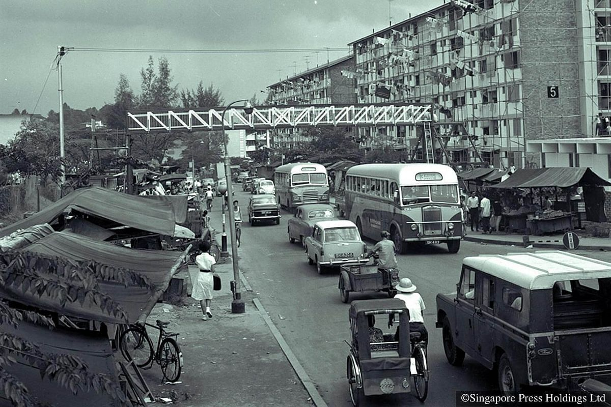 1967: An overhead bridge under construction over a busy Tiong Bahru Road,  in front of a block of  flats.  In this year, the Land Acquisition Act enabled HDB to clear slums and squatters to free up land for public housing and infrastruture developmen