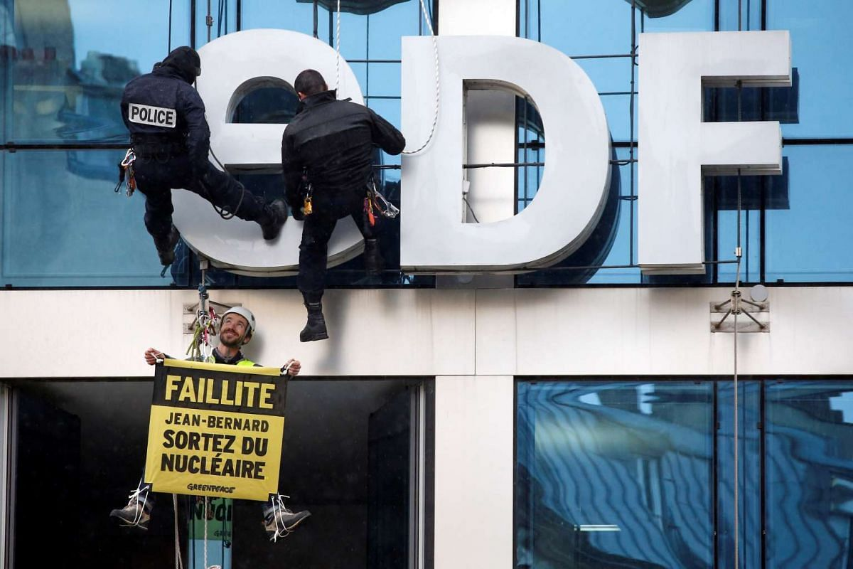 """French police intervene as a Greenpeace activist hangs a banner which reads """"EDF is bankrupt, let's phase out nuclear power"""" on the facade of the France's state-owned electricity company EDF headquarters during the company's 2016 annual results prese"""