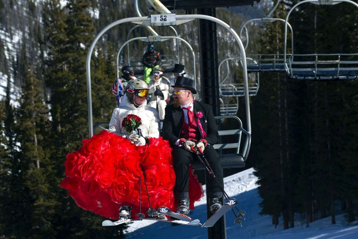 Karyn (L) and husband Tucker Brown (R) ride the Ptarmigan chair lift while celebrating their 10th wedding anniversary during the Loveland Ski Area 26th Annual Valentine's Day Mountaintop Matrimony held near Georgetown, Colorado on February 14, 2017.