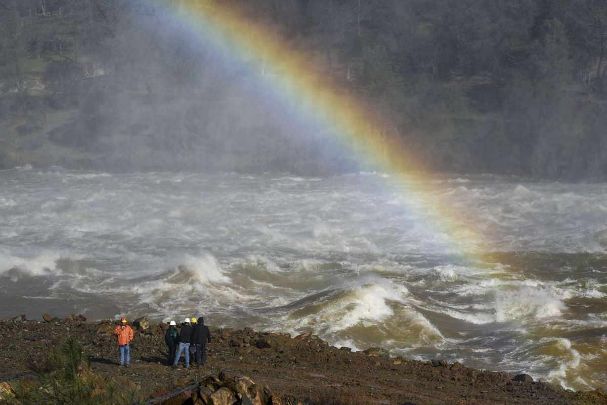 A rainbow is seen next to Department of Water Resources workers on the banks of the Feather River as water is released down the damaged primary spillway at 100,000 cubic feet per second in Oroville, California, U.S., on Tuesday, February 14, 2017. PH