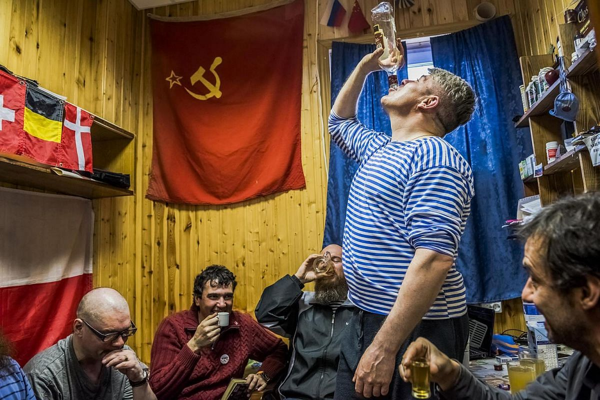 The winter expedition crew of Russian research team and a Chilean scientist drink Samagon, a homemade vodka, in a bedroom of the Bellingshausen Antarctica base; Fildes Bay, Antartica, on Nov 28, 2015.