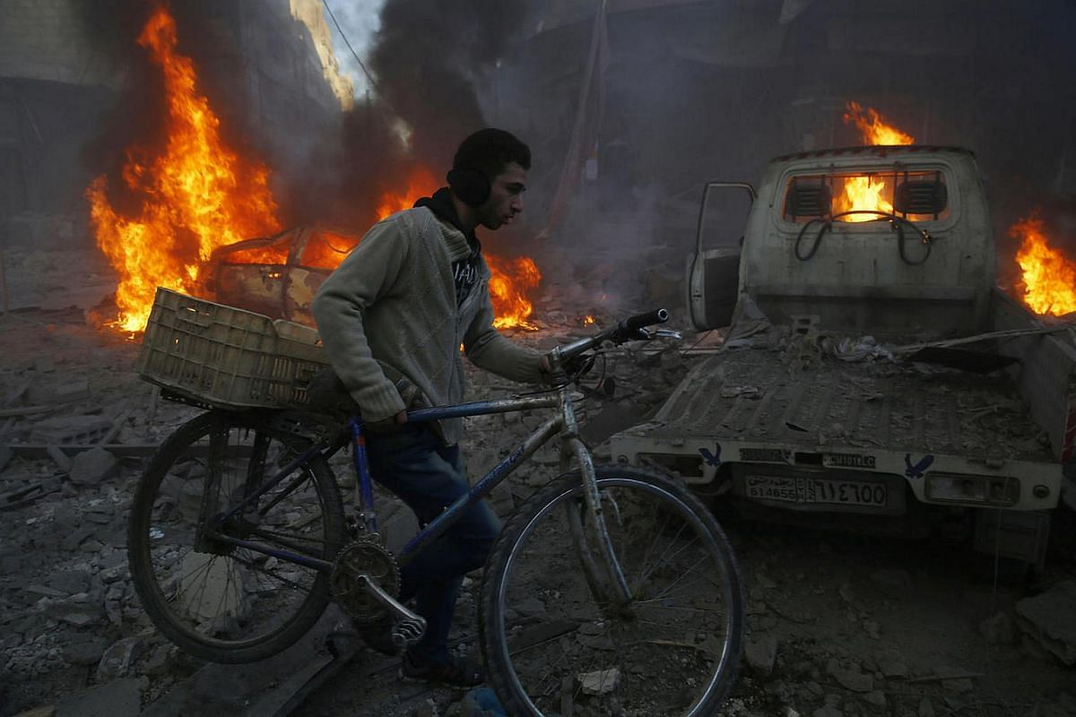 A man pushes his bicycle past debris following airstrikes in Hamouria, Syria.