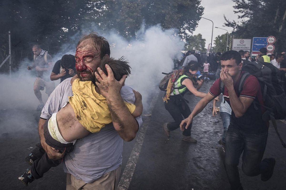 A man carries his child as Hungarian police use tear gas, pepper spray and water cannons against people trying to cross into the country from Serbia, the day after Hungary closed its border with Serbia.