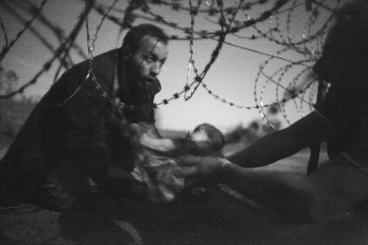 A baby is handed through a hole in a razor wire barrier, to a Syrian refugee who has already managed to cross the border from Serbia into Hungary, near Röszke. Hungary was hardening its stance towards refugees attempting to enter the country. In Jul