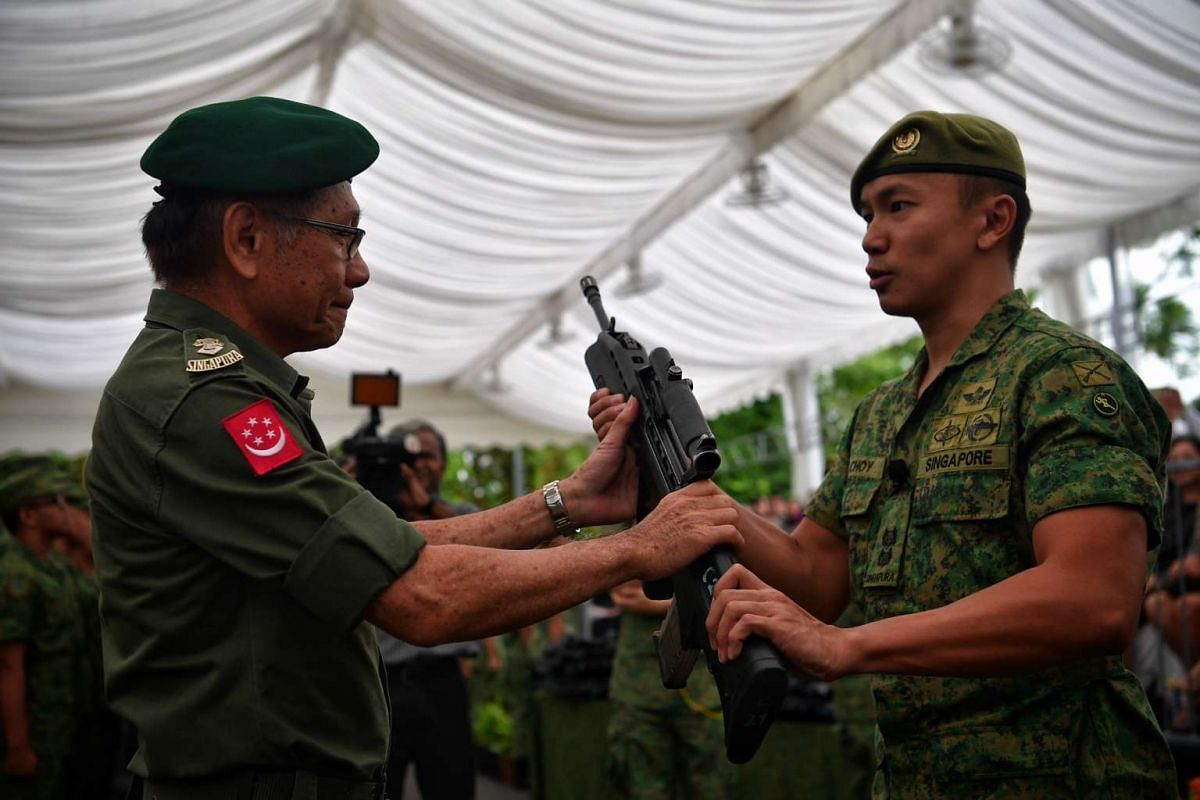 71-year-old SAF veteran LTC Swee Boon Chai handing CO LTC Choy Yong Cong a rifle during the weapon presentation ceremony held before the launch of the new World War II exhibition.