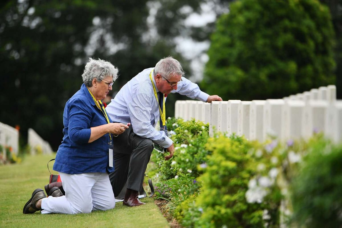 Mr Neil Munro (right) and Mrs Clare Munro looking at tombstone of her father's brother, after the remembrance ceremony at Kranji War Cemetery, on Feb 15, 2017.