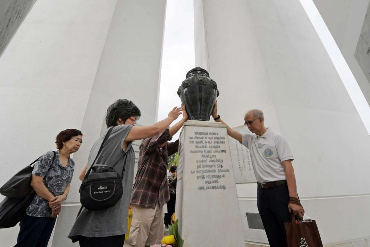 Visitors laying their hands on the urn at the Memorial to the Civilian Victims of the Japanese Occupation.