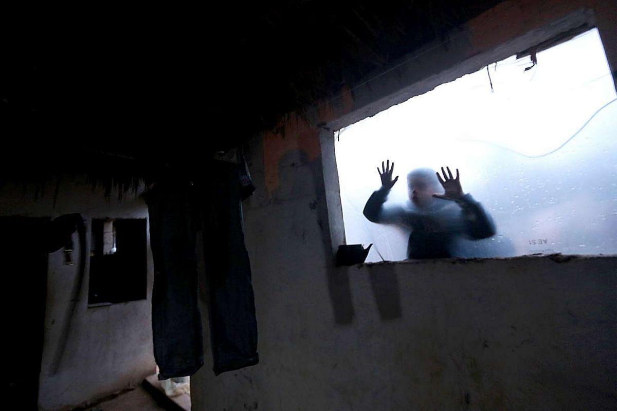 A Palestinian boy play in his family makeshift house during rainy and cold weather in the north Gaza City on, February 16, 2017. PHOTO: EPA