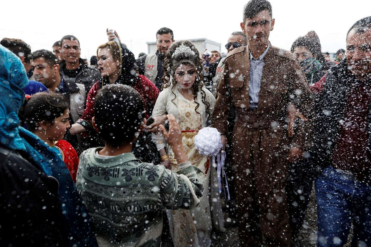 Iraqi newlyweds, who fled Mosul, Hussain Zeeno Zannun (R) 26, and Chahad, 16, are showered in foam during their wedding party at Khazer camp in Iraq February 16, 2017. PHOTO: REUTERS