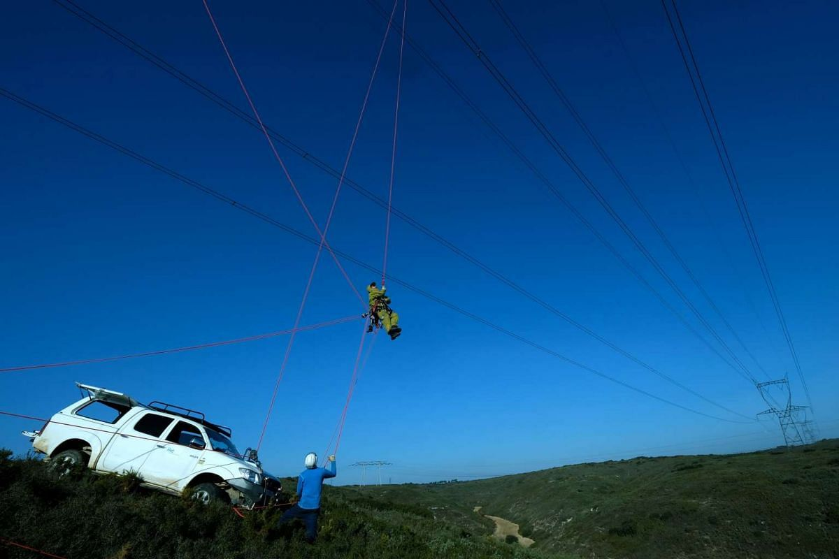 Technicians from the RTE (Reseau de Transport d'Electricite) install a sensor, capable of measuring the cooling effect of the mistral on a high-voltage line, on a 400,000 volt power line in Aix-en-Provence on February 16, 2017. PHOTO: AFP