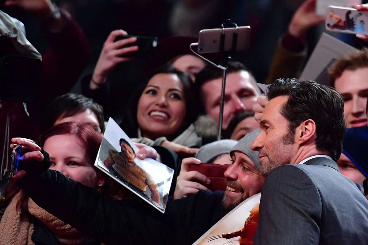 Hugh Jackman poses for photos with fans as he arrives for the premiere of the film Logan at the 67th Berlinale film festival in Berlin on Feb 17, 2017.