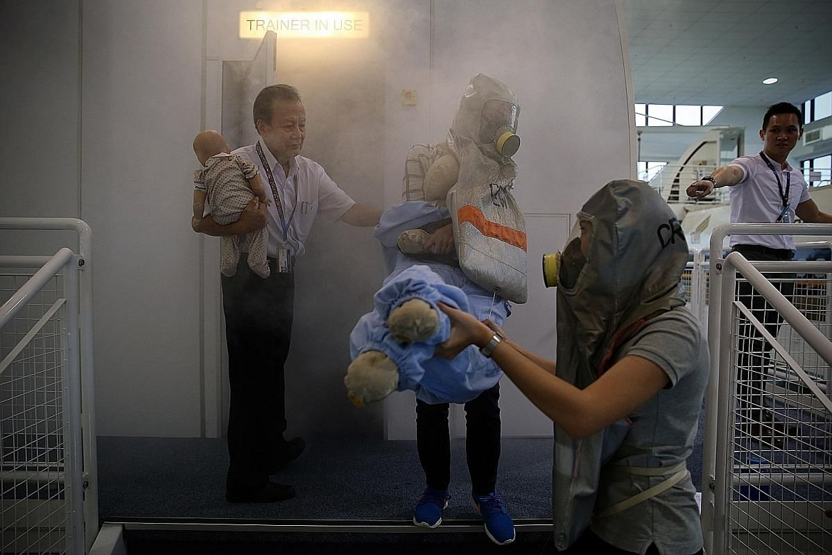 Cabin crew trainees observe a fellow trainee learning to use the fire extinguisher under the guidance of an instructor. They also learn how to manage oven and toilet fires, and practise donning the smoke hood - available at all doors on the aircraft