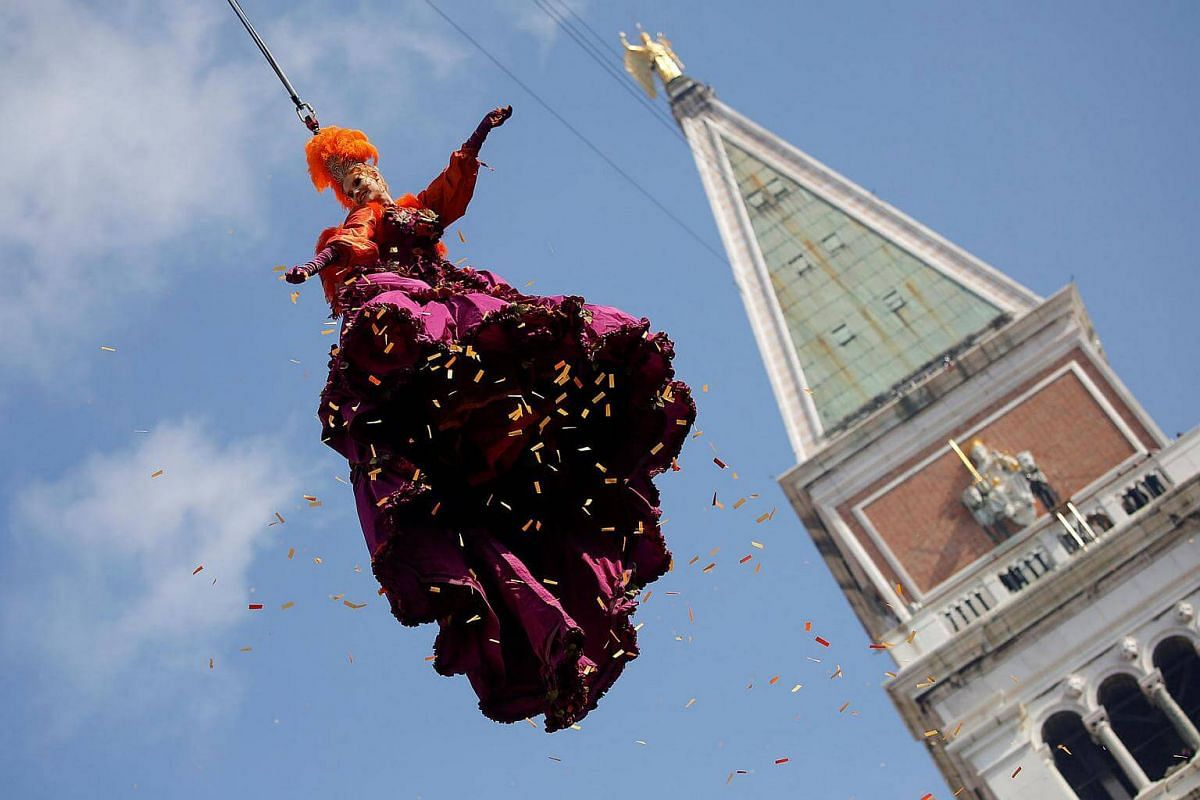 "A woman dressed as an ""angel"" descending on Saint Mark's Square during the Venice Carnival, Italy, on Feb 19, 2017."