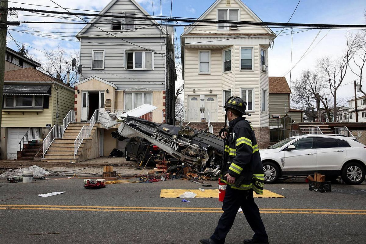 An official surveying the scene where a small plane crash landed on a residential street in Bayonne, New Jersey, US, on Feb 19, 2017.