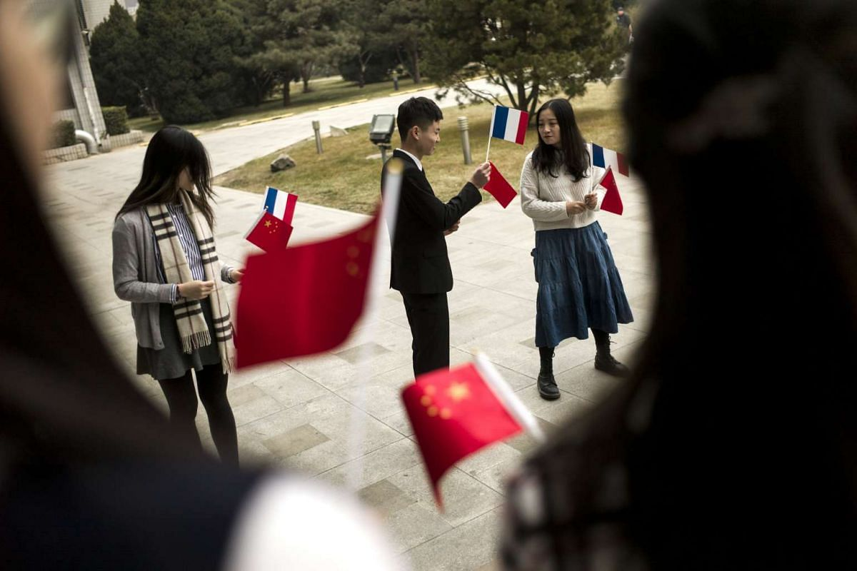 Students holding the national flags of France and China before the arrival of French Prime Minister Bernard Cazeneuve at Beida University in Beijing, China, on Feb 21, 2017.