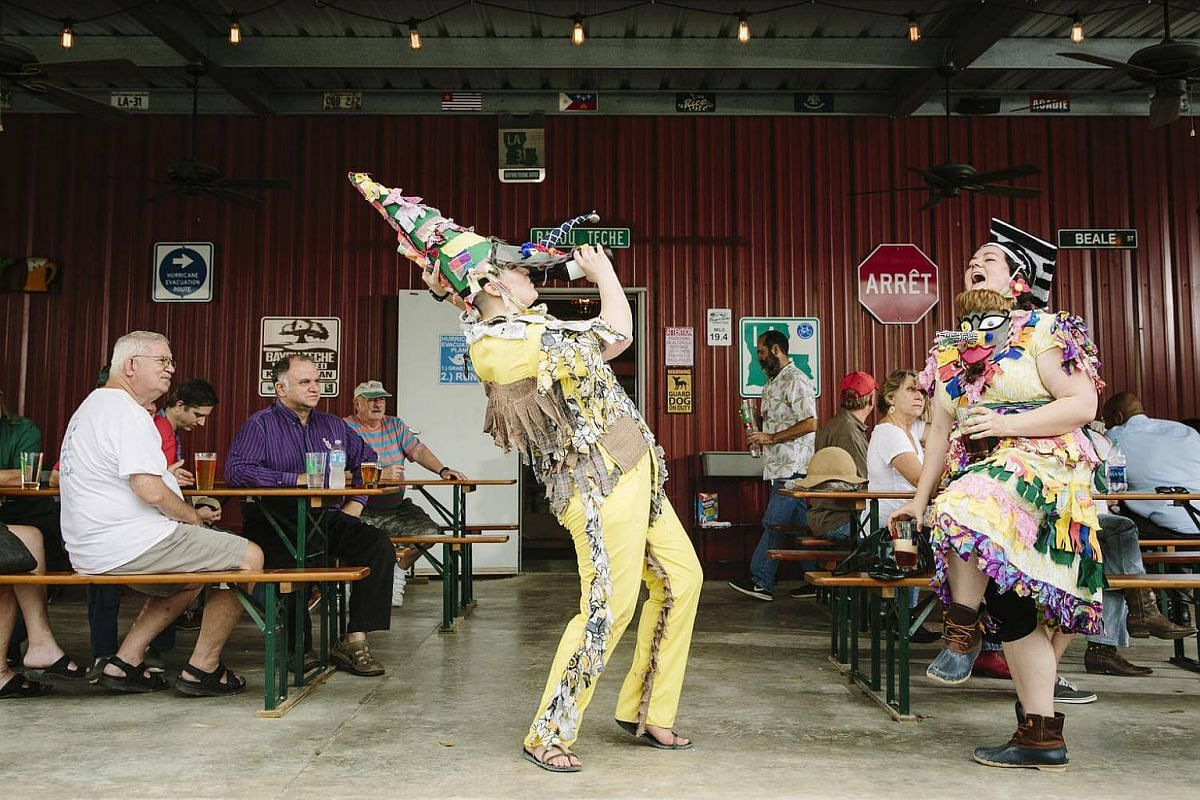 Lizzy Waters (left) and Lian Cheramie dancing in traditional Courir de Mardi Gras costumes at the Bayou Teche Brewery in Arnauldville, La., on Feb 11, 2017.