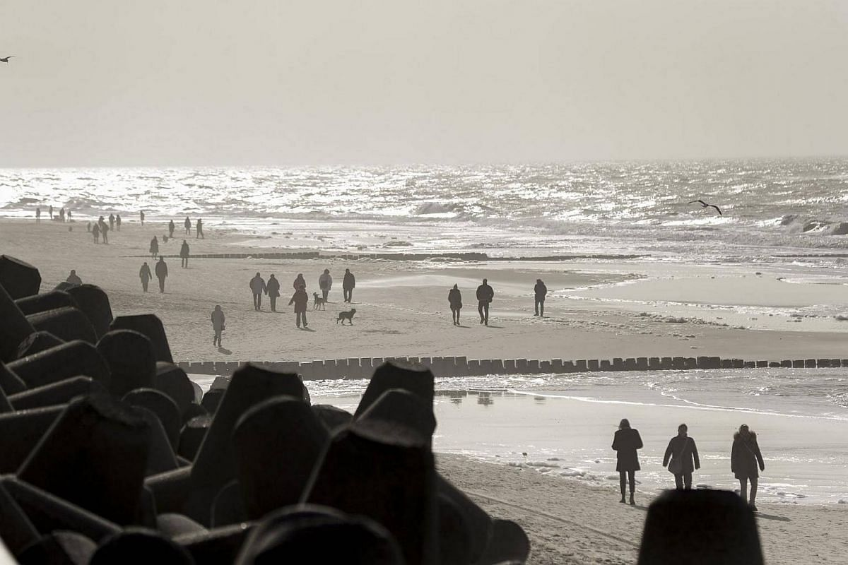 People enjoying a sunny weather as they walk on the beach of the North Sea in Westerland on the Sylt Island, Germany, on Feb 21, 2017.