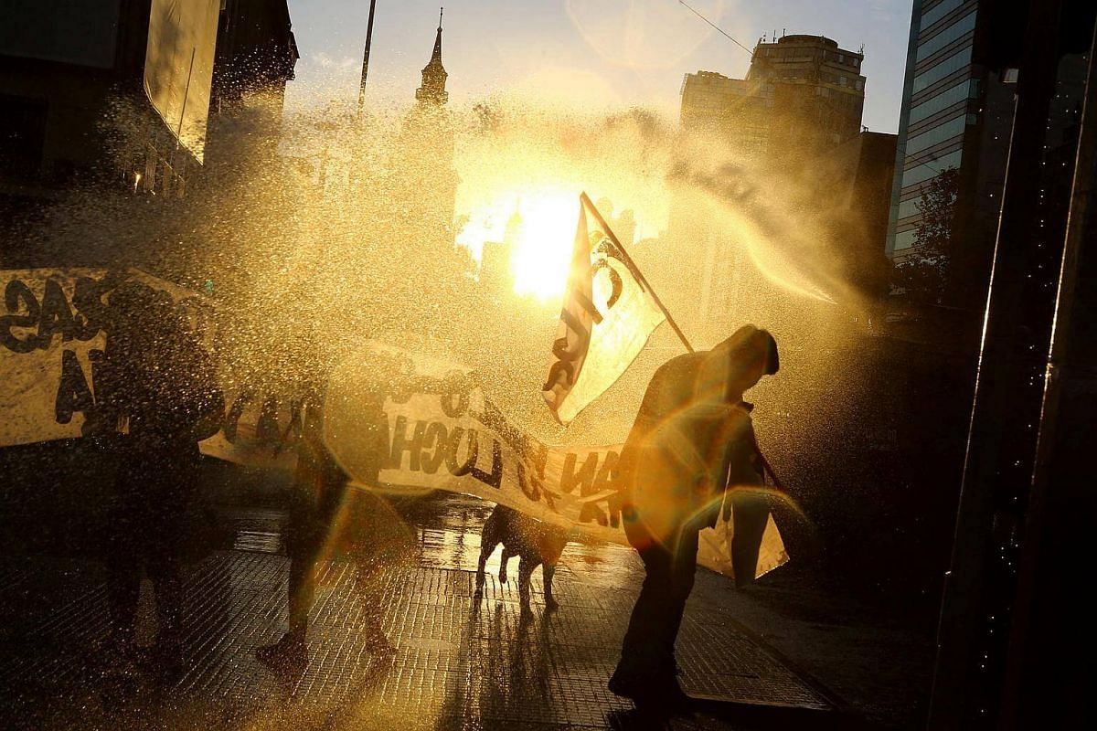 A jet of water is released on protesters during a rally marking the anniversary of the death of union leader Juan Pablo Jimenez, in Santiago, Chile, on Feb 21, 2017.