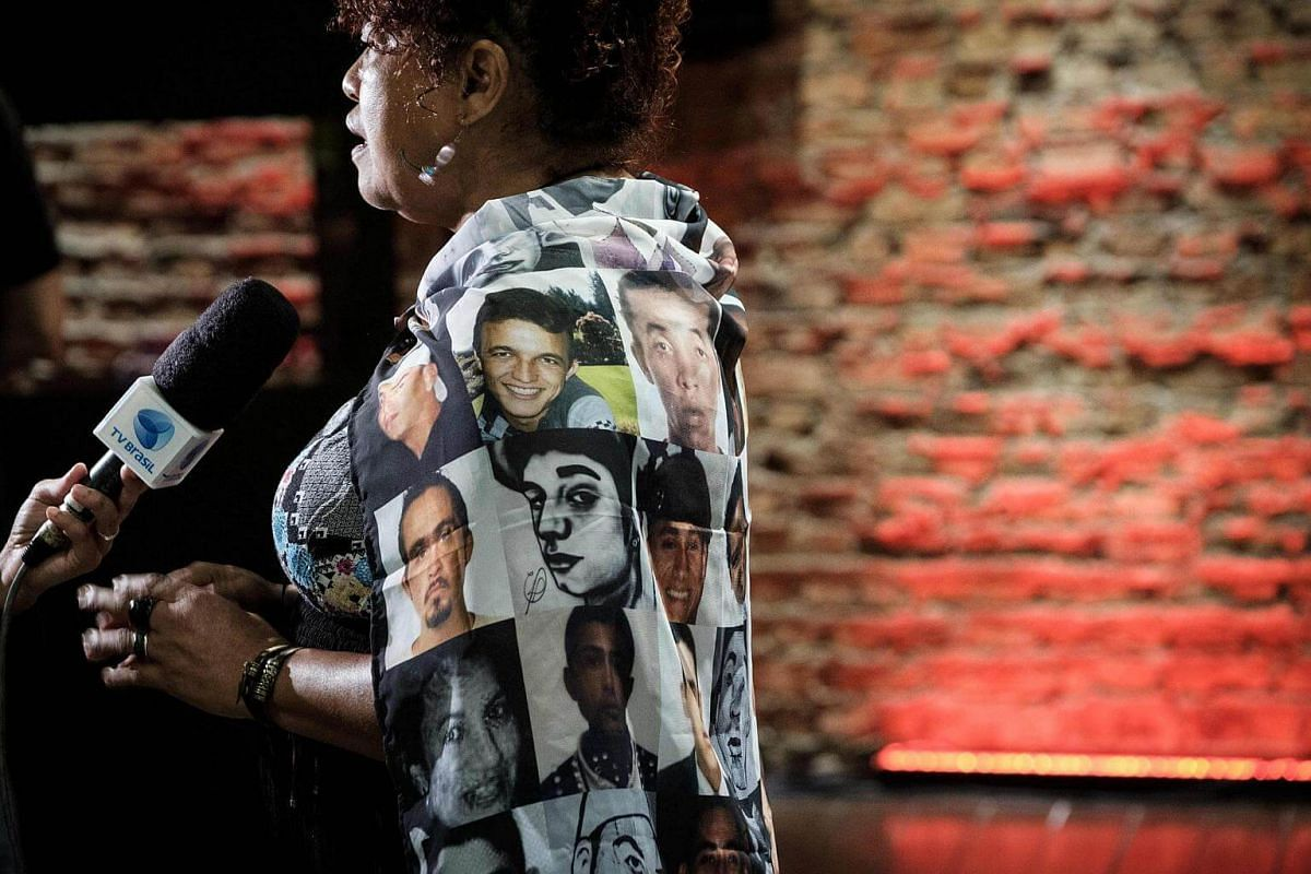 Mrs Debora Silva, a founder of Maes de Maio and the mother of 29-year-old son Edson Rogerio da Silv,a who was shot dead by police in 2006, speaking to media as she wears a scarf with images of victims by police shooting, during human rights organisat