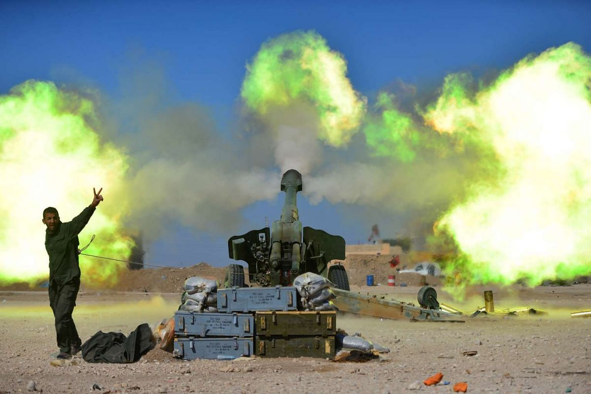Popular Mobilization Forces troopers firing an artillery piece at Islamic State militants during a battle, west of Mosul, on Feb 22, 2017.
