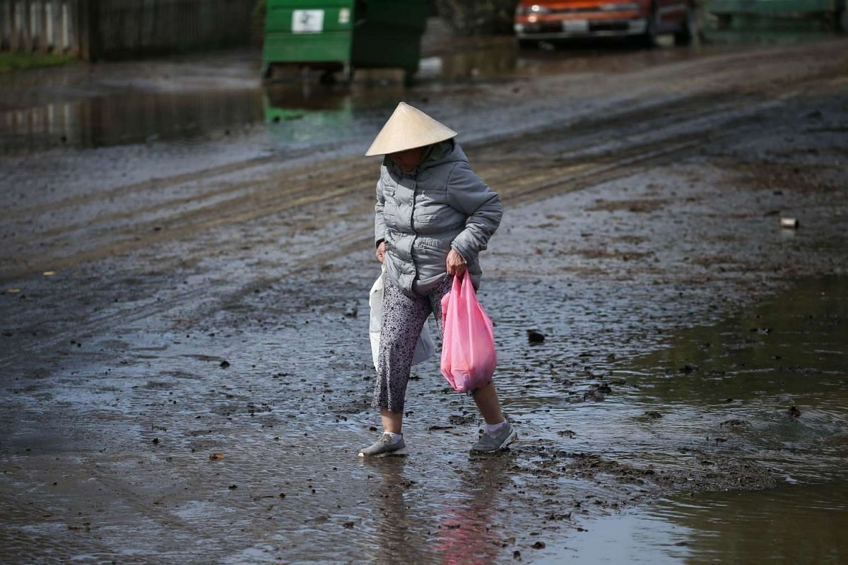 A woman walking through mud with some of her personal belongings, following flooding in San Jose, California, on Feb 22, 2017.
