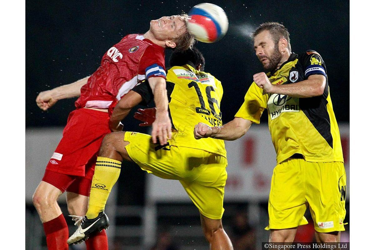2013: Balestier Khalsa's captain and striker, Paul Cunningham bends over backwards in an aerial duel with Tampines Rovers' Mustafic Fahrudin and Seiji Kaneko at Toa Payoh Stadium. The New Zealander  was named TNP Man of the Match.