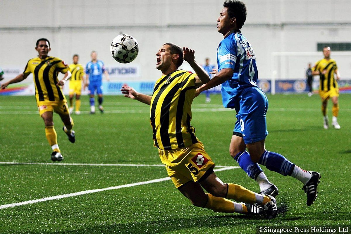 2009: DPMM Brunei's Rene Komar (in yellow jersey) falls as he tried to block Tampines Rovers' striker Noh Alam Shah during a S-League match that ended in a 1-1 draw. DPMM became the second foreign team to win the S.League title in 2015.