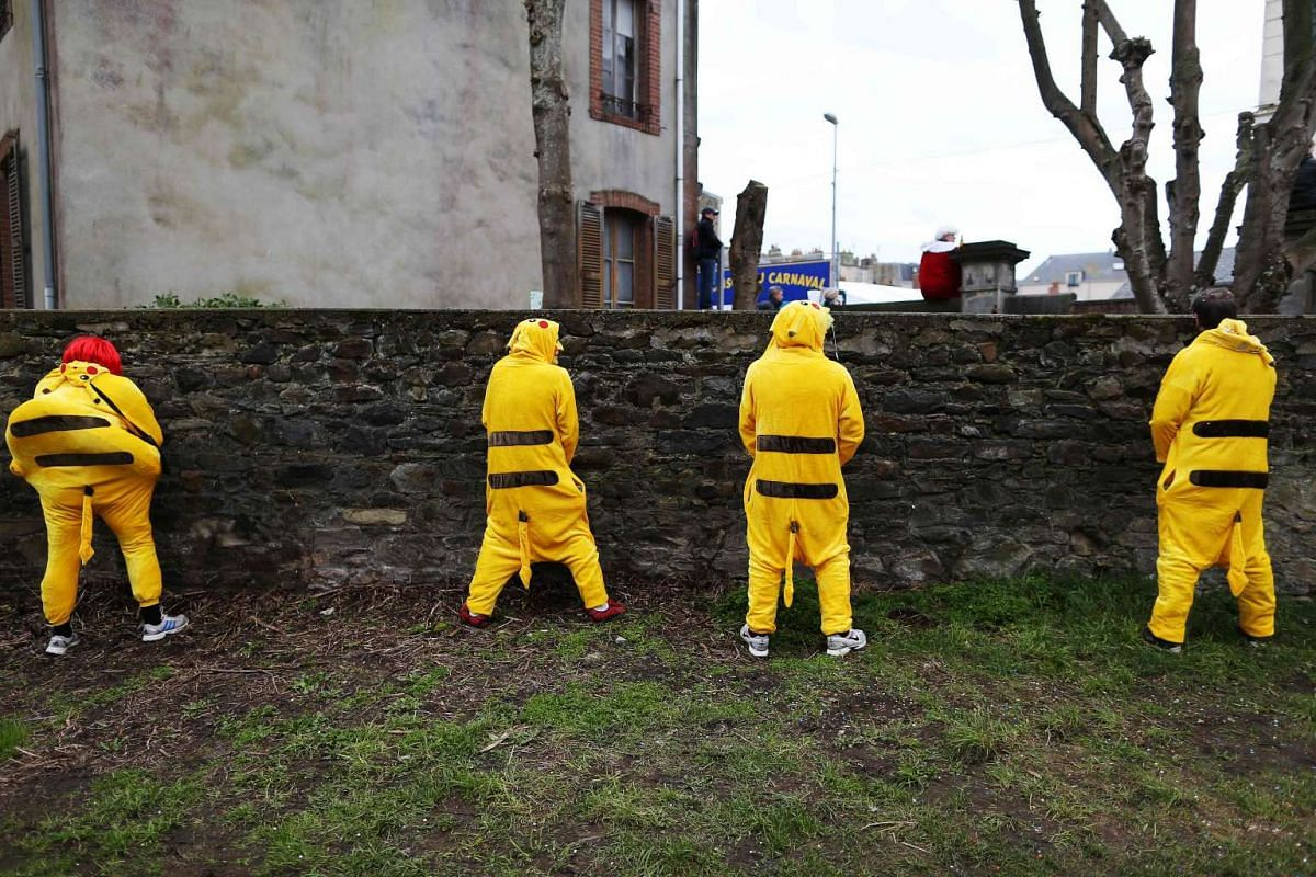 People dressed in costume urinating on a wall during the annual UNESCO-listed Carnival Of Granville in France on Feb 26, 2017.