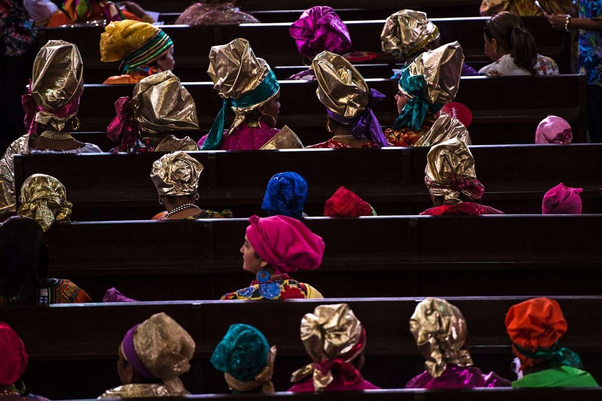 Women dressed as madamas attending a mass before the beginning of the Carnival Of El Callao in the Venezuelan state of Bolivar on Feb 26, 2017. Madamas are the pillars of Callaoense identity, representing Antillean matrons, who are considered the com
