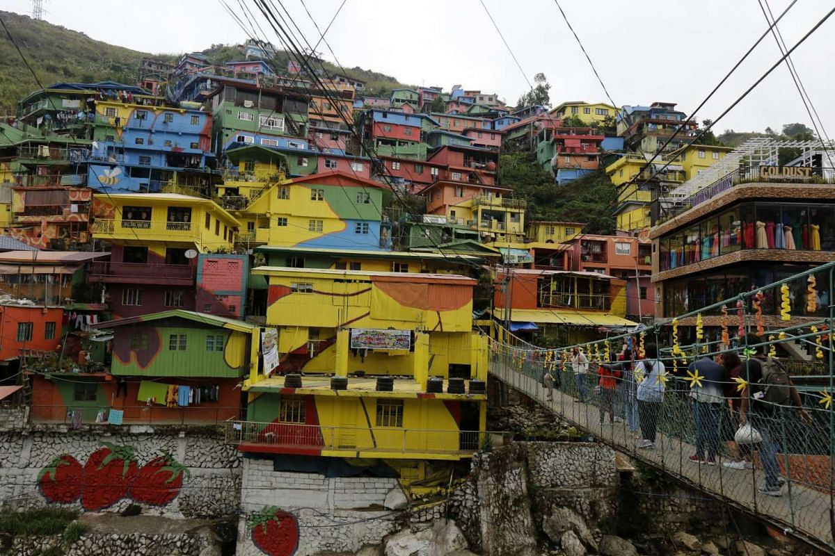Tourists on a makeshift bridge next to houses painted in different colours at the edge of a mountain in the town of La Trinidad, Benguet province, Philippines, on Feb 26, 2017.