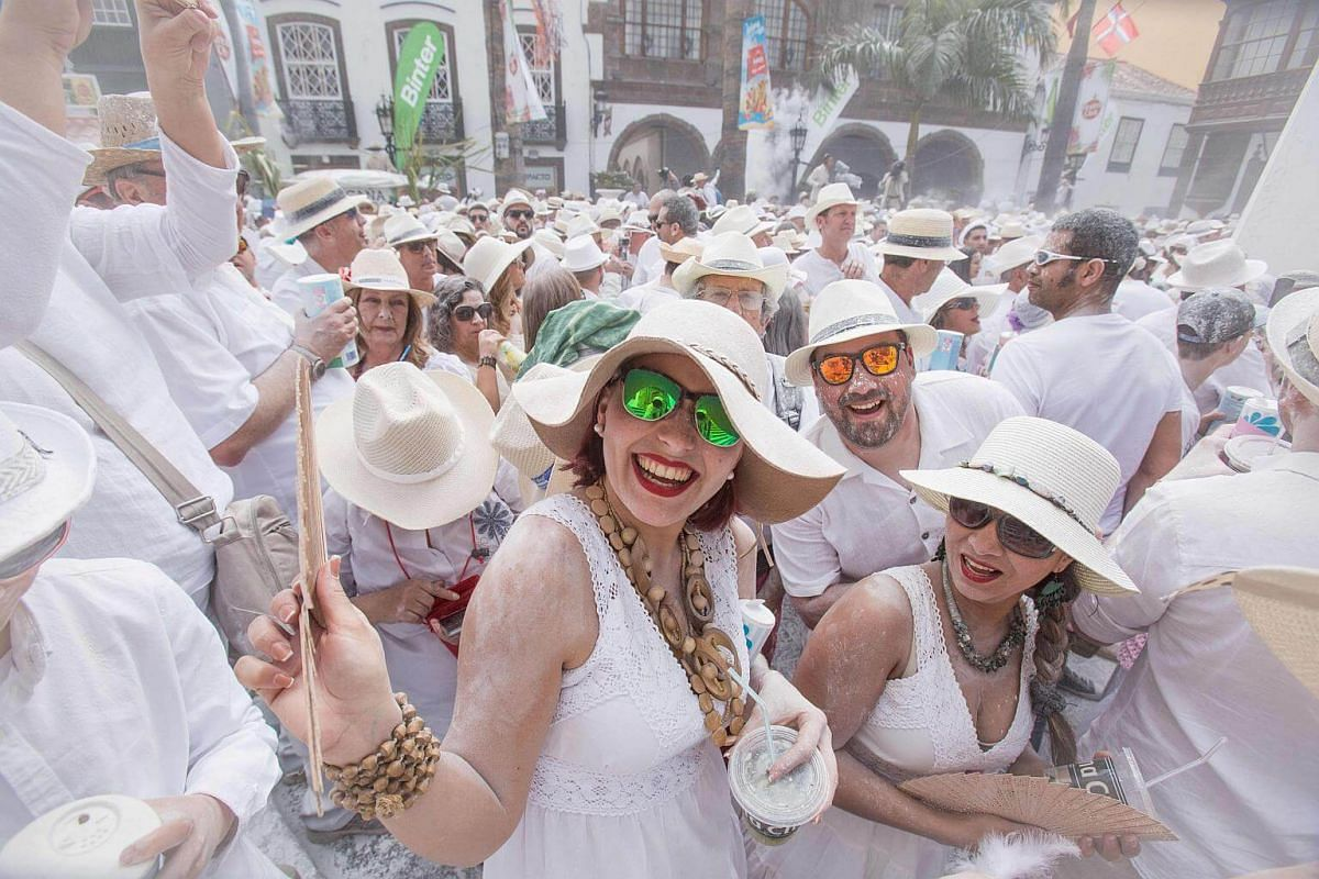Revellers covered with talcum powder wait for promotional goodies during the street carnival Los Indianos in Santa Cruz de la Palma, on the Spanish Canary island of La Palma.