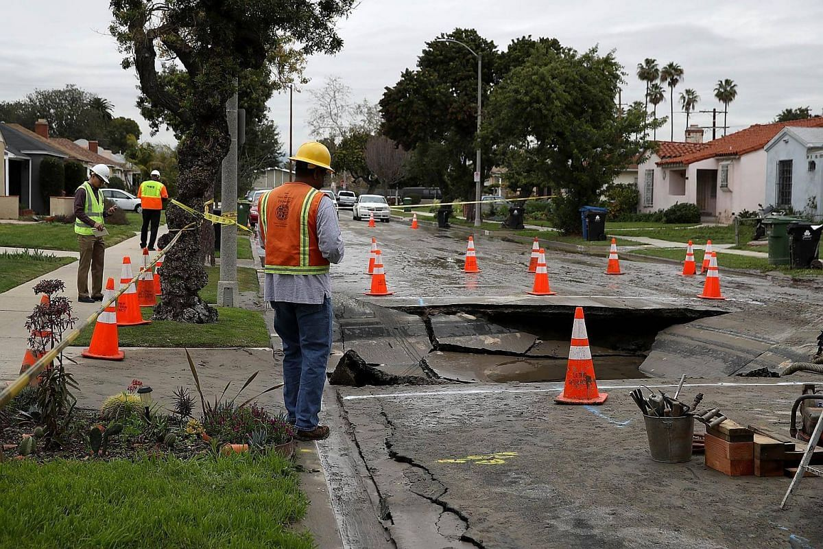 Los Angeles Department of Water and Power (Ladwp) workers inspect a massive sinkhole on West Boulevard in Los Angeles, California.