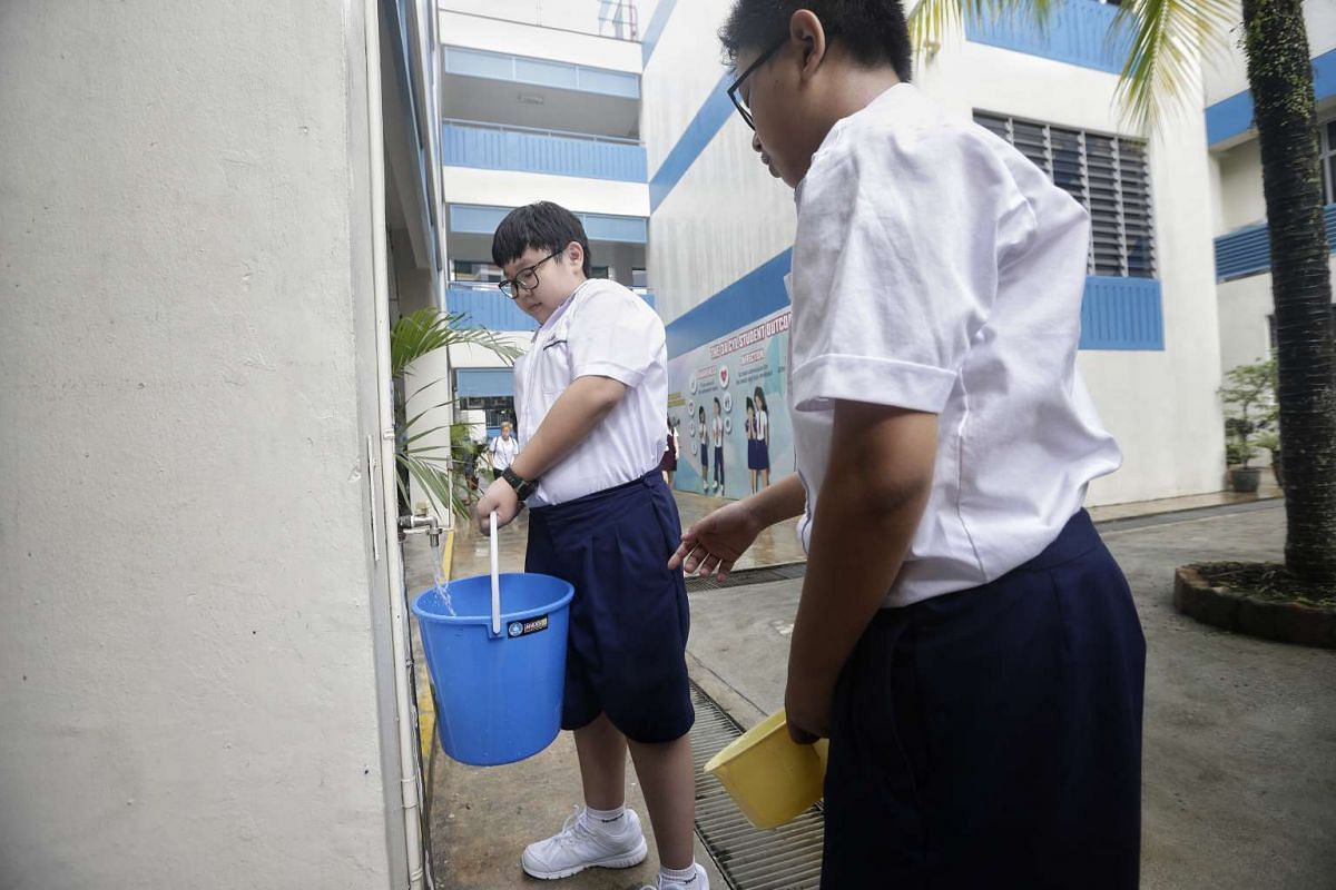 Students collecting water from tap during a water rationing exercise at Woodgrove Secondary School, on March 1, 2017.