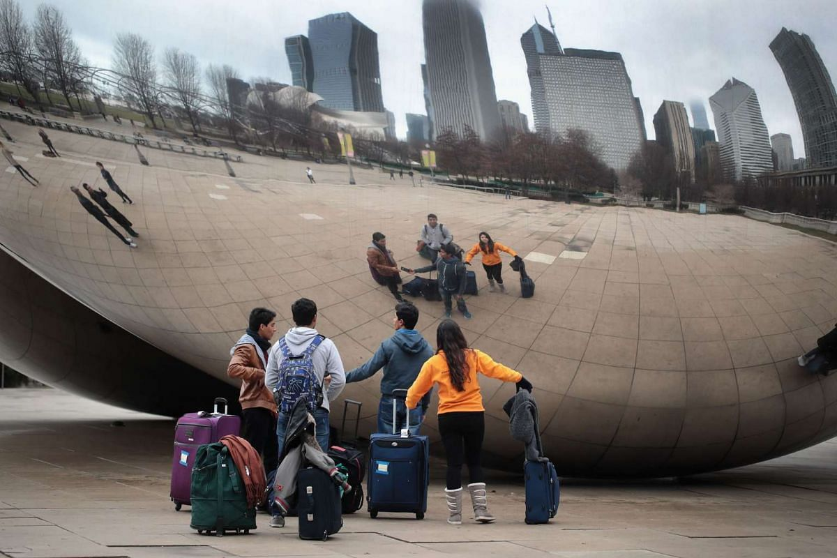 Visitors looking over the Cloud Gate sculpture in Millennium Park in Chicago, Illinois, on Feb 28, 2017.
