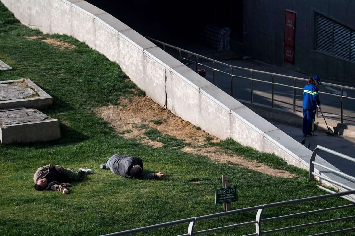 Two men sleeping on a grass field in front of the Shanghai South Railway Station on Feb 28, 2017.