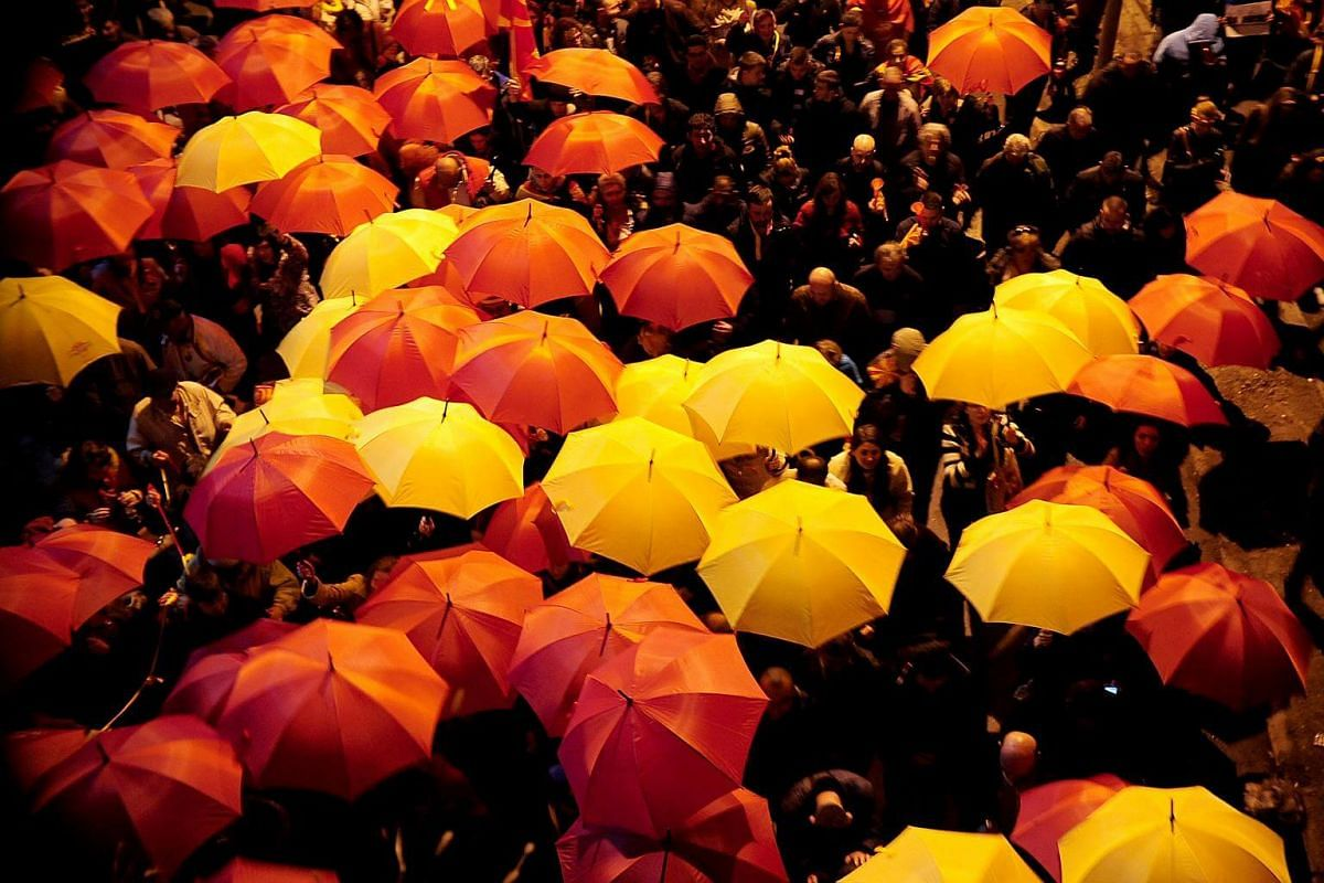 Protesters shouting slogans while holding red and yellow umbrellas during demonstrations against an agreement that would ensure the wider official use of the Albanian language, in Skopje, Macedonia, on March 1, 2017.