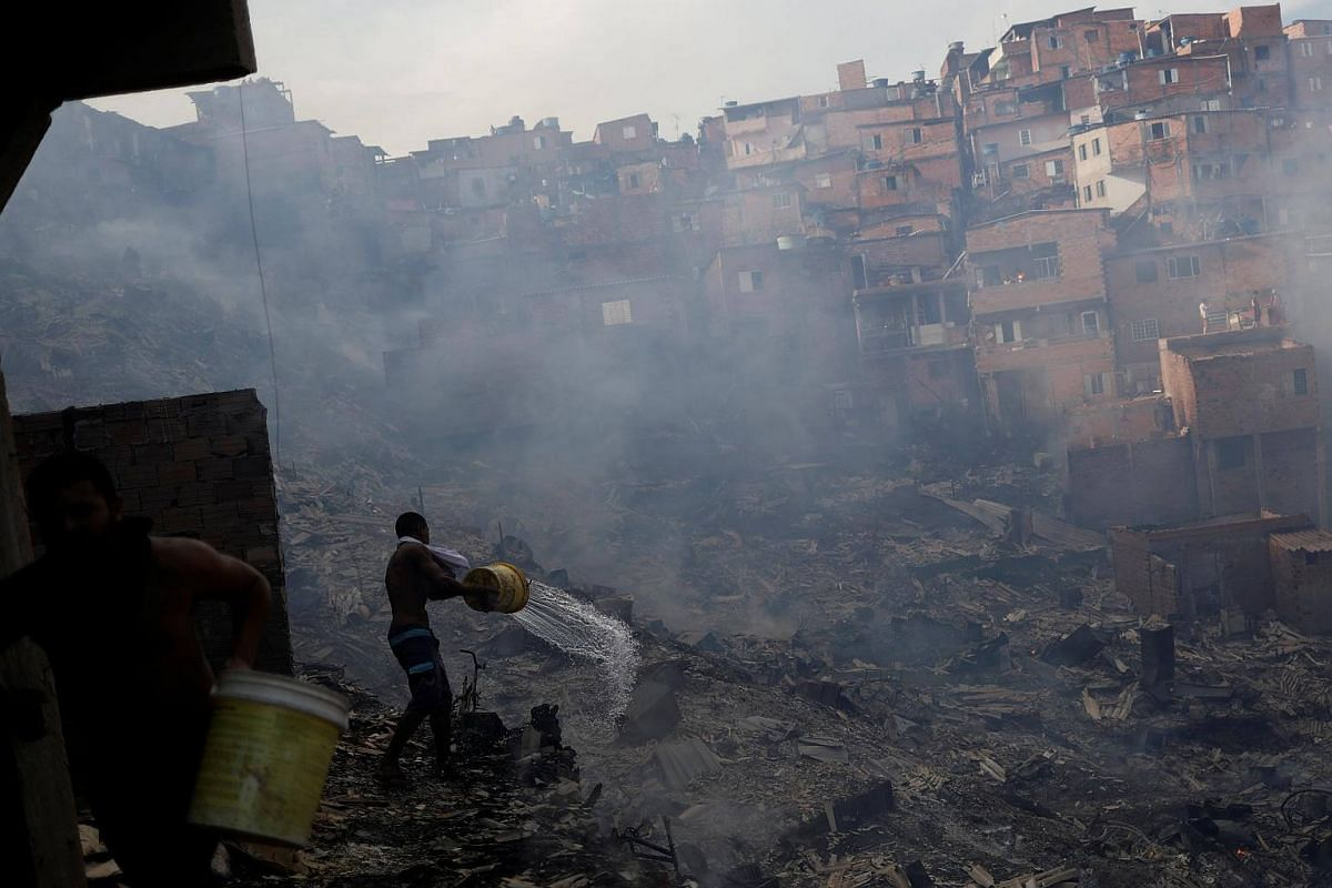 Residents pouring water from their houses as they try to extinguish a fire in the Paraisopolis slum in Sao Paulo, Brazil, on March 1, 2017.
