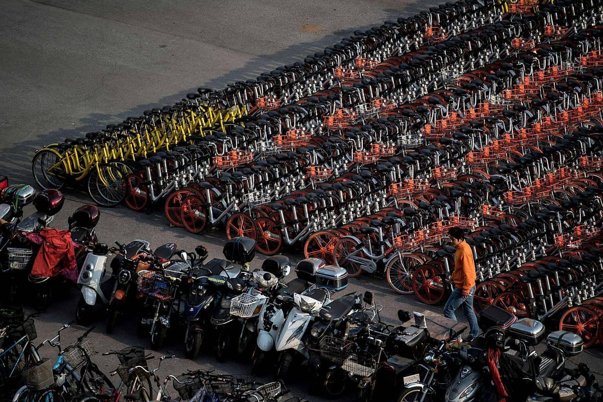 A man walking past impounded bicycles from the bike-sharing schemes Mobike and Ofo in Shanghai, China, on March 1, 2017.
