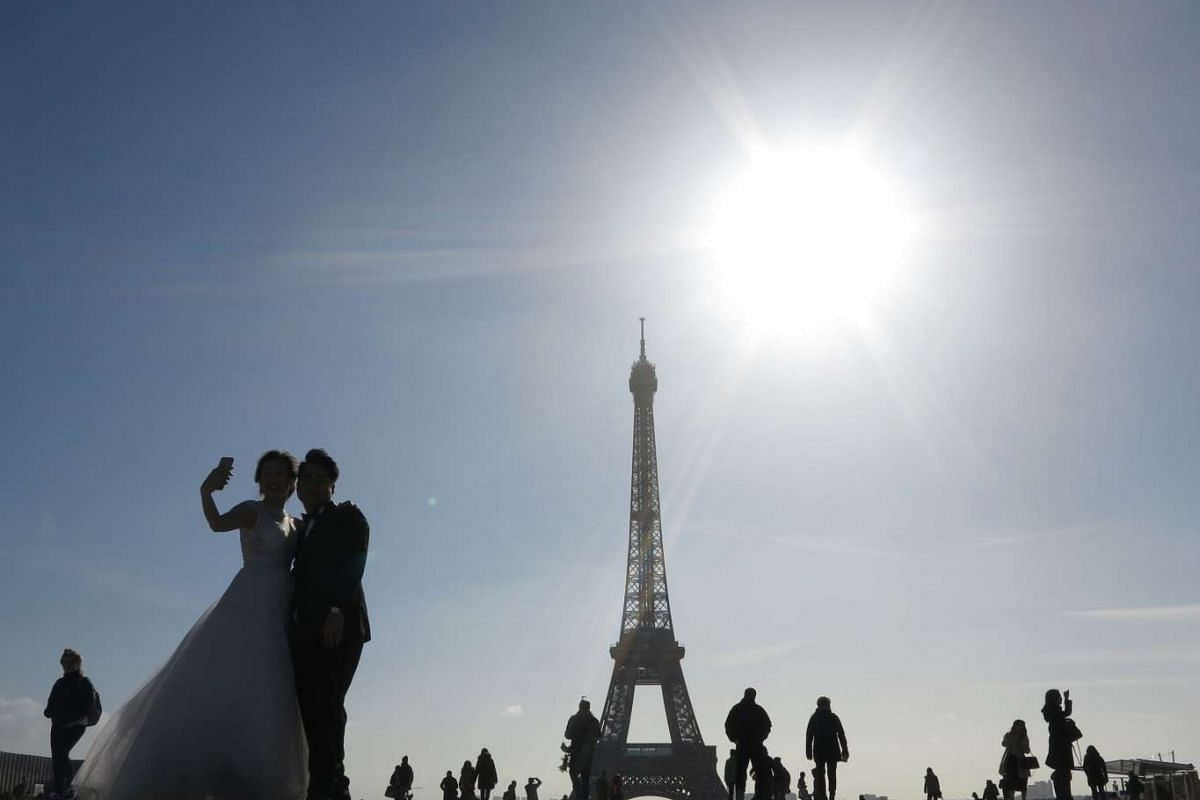 A newly-wed couple takes a selfie on Trocadero square in front of The Eiffel Tower on a sunny morning on March 02, 2017, in Paris.