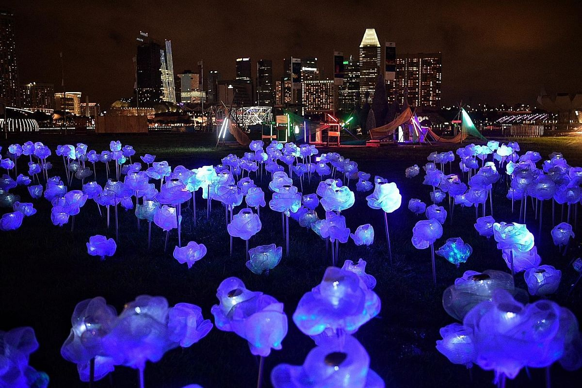 Four-year-old Sophia Shi, a tourist from Beijing, having fun at Home, an installation by Anna Galas of Poland. MoonFlower is a display of 800 flowers that Singaporean artist Lee Yun Qin created using plastic netting. Each flower is lit with a solar-p