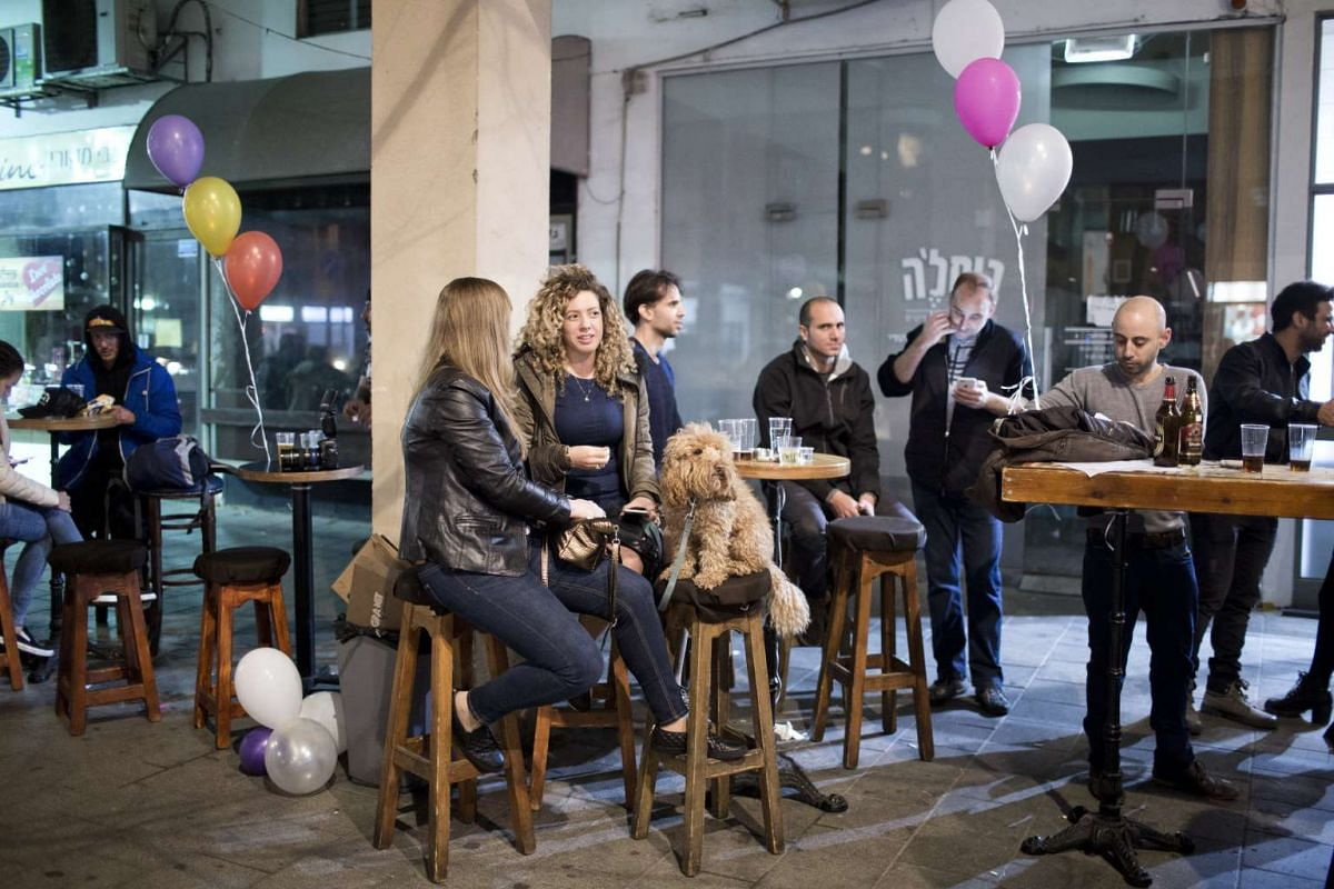 People sitting with their dog in a bar in Tel Aviv, Israel, on Feb 25, 2017.